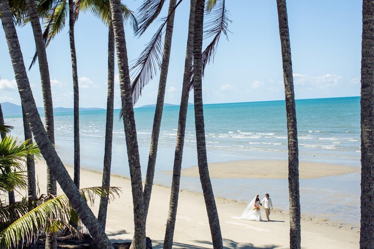 Häät ulkomailla | Hääpari kävelee rannalla palmujen takana.