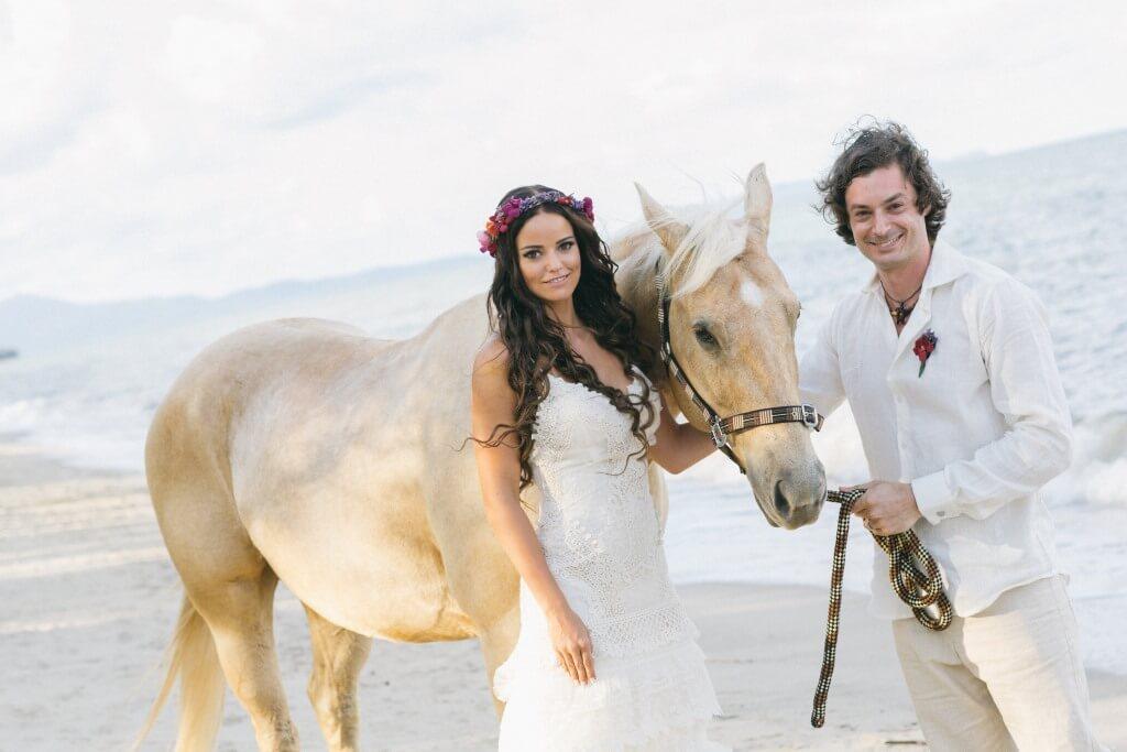 Häät ulkomailla | Hääpari rannalla hevosen kanssa.