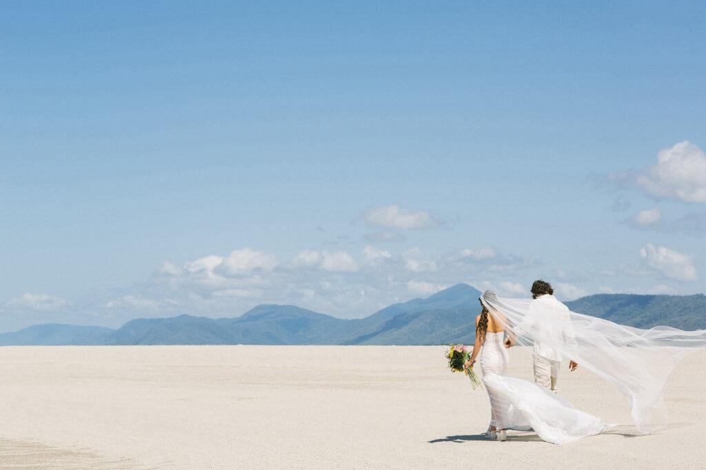 Häät ulkomailla | Hääpari kävelee rannalla.