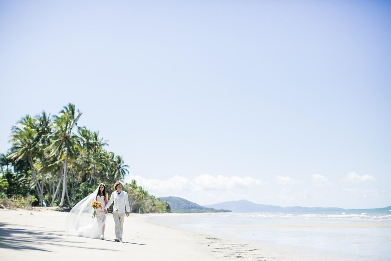 Destination Wedding | Hääpari kävelee palmurannalla.